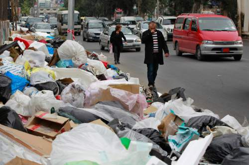 In this Thursday, Dec. 17, 2015 photo, Lebanese citizens pass by a pile of garbage on a street in Beirut, Lebanon. Lebanon's trash collection crisis which set off summer protests is entering its sixth month, but you would hardly be able to know it in Beirut. (AP Photo/Bilal Hussein)