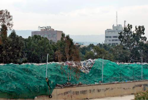 In this Thursday, Dec. 17, 2015 photo, a pile of garbage blocks a street covers by  a green tarp in Karantina, east Beirut, Lebanon. Lebanon's trash collection crisis which set off summer protests is entering its sixth month, but you would hardly be able to know it in Beirut. (AP Photo/Bilal Hussein)