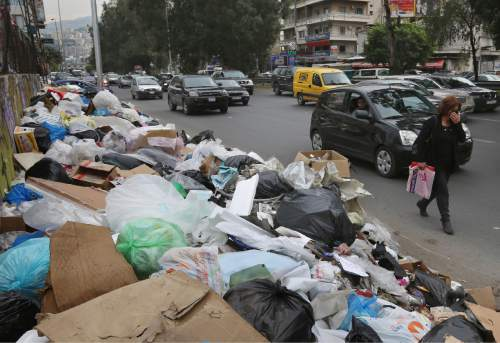 In this Thursday, Dec. 17, 2015 photo, a Lebanese woman covers her nose from the smell as she passes by a pile of garbage on a street in Beirut, Lebanon. Lebanon's trash collection crisis which set off summer protests is entering its sixth month, but you would hardly be able to know it in Beirut. (AP Photo/Bilal Hussein)