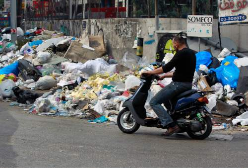 In this Thursday, Dec. 17, 2015 photo, a Lebanese man rides a motorcycle as he passes by a pile of garbage on a street in Beirut, Lebanon. Lebanon's trash collection crisis which set off summer protests is entering its sixth month, but you would hardly be able to know it in Beirut. (AP Photo/Bilal Hussein)
