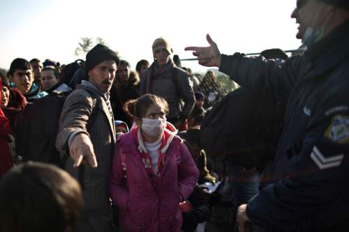 In this Saturday, Dec. 5, 2015 photo, Yazidi refugee Samir Qasu, 45, center, from Sinjar, Iraq, and his  daughter Dunia, 13, gestures to a Greek police officer while he an d his family and other refugees and migrants wait to be permitted to cross the Greek-Macedonian border, near the northern Greek village of Idomeni.  Within two days of arriving on Lesbos, the Qasus had traveled by midnight ferry from Lesbos to Athens and then by bus to Greece's northern border with Macedonia.  (AP Photo/Muhammed Muheisen)