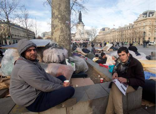 Afghan migrants camp out on the Place de la Republique in Paris, Tuesday, Dec. 22, 2015. Dozens of  Afghan migrants chose the site of the Paris attacks memorial to call attention to their lack of housing. (AP Photo/Jacques Brinon)