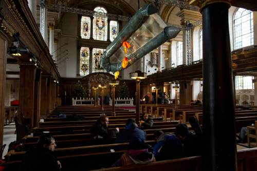 People taking shelter sit on the pews in the foreground beneath a salvaged dinghy, together with three life jackets, two adults' size and a child's, hanging suspended in the nave of St James's Church, Piccadilly, forming an installation entitled 'Flight' by artist Arabella Dorman in London, Tuesday, Dec. 22, 2015. The boat is designed to carry 15 people, but transported 62 refugees, many from Syria, across 10kms of rough sea from Assos, Turkey, to Lesbos in Greece, with all onboard surviving the journey. (AP Photo/Matt Dunham)