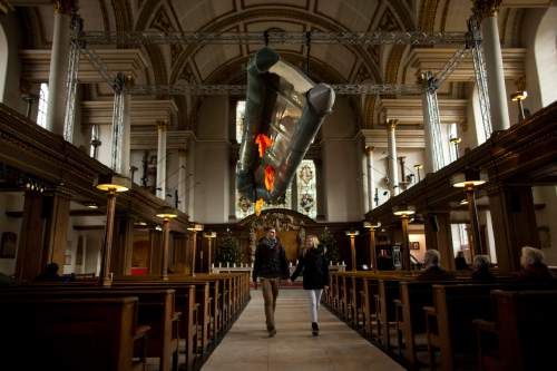Tourists walk holding hands beneath a salvaged dinghy, together with three life jackets, two adults' size and a child's, hanging suspended in the nave of St James's Church, Piccadilly, forming an installation entitled 'Flight' by artist Arabella Dorman in London, Tuesday, Dec. 22, 2015. The boat is designed to carry 15 people, but transported 62 refugees, many from Syria, across 10km of rough sea from Assos, Turkey, to Lesbos in Greece, with all onboard surviving the journey. (AP Photo/Matt Dunham)