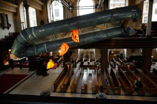 A salvaged dinghy, together with three life jackets, two adults' size and a child's, hangs suspended in the nave of St James's Church, Piccadilly, forming an installation entitled 'Flight' by artist Arabella Dorman in London, Tuesday, Dec. 22, 2015. The boat is designed to carry 15 people, but transported 62 refugees, many from Syria, across 10km of rough sea from Assos, Turkey, to Lesbos in Greece, with all onboard surviving the journey. (AP Photo/Matt Dunham)