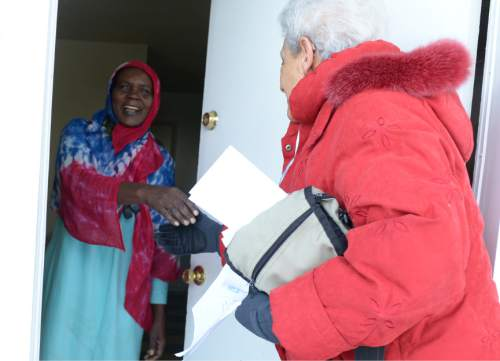 Leah Hogsten  |  The Salt Lake Tribune Sudanese refugee Fatime Yaya  smiles as Shalom, Salaam ñ Tikkun Olam volunteer Lois Speigel hands her gifts for her family of four at her home on Friday. Shalom, Salaam ñ Tikkun Olam Christmas Day Project, a project that reaches hundreds in need, including 100 refugee families and 350 seniors, as well as residents of area shelters. The charity includes more than 300 volunteers from diverse religious, cultural, and educational backgrounds who prepare and deliver packages made up of food, household goods, gifts, and gift cards, all of which are donated by participating retailers or purchased with donated funds.