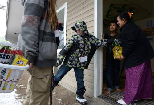 Leah Hogsten  |  The Salt Lake Tribune Hassan Abdul and his mother Hasena Osman, refugees from Burma, smile as Jefferey Griffith (center), his mother Mary Griffith and his brothers deliver gifts on Christmas day, December 25, 2015 to their home.  Shalom, Salaam – Tikkun Olam Christmas Day Project, is a project that reaches hundreds in need, including 100 refugee families and 350 seniors, as well as residents of area shelters. The charity includes more than 300 volunteers from diverse religious, cultural, and educational backgrounds who prepare and deliver packages made up of food, household goods, gifts, and gift cards, all of which are donated by participating retailers or purchased with donated funds.