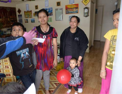 Leah Hogsten  |  The Salt Lake Tribune l-r Hassan Abdul, sister Farida, mother Hasena Osman, and sister Sofiya, refugees from Burma, receive gifts on Christmas day, December 25, 2015 to their home.  Shalom, Salaam – Tikkun Olam Christmas Day Project, is a project that reaches hundreds in need, including 100 refugee families and 350 seniors, as well as residents of area shelters. The charity includes more than 300 volunteers from diverse religious, cultural, and educational backgrounds who prepare and deliver packages made up of food, household goods, gifts, and gift cards, all of which are donated by participating retailers or purchased with donated funds.