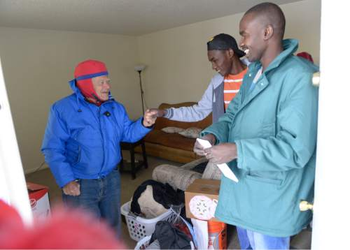 Leah Hogsten  |  The Salt Lake Tribune Sudanese refugee Yacoub Arbab, 24, and his brother Hisseine Arbab smiles as Shalom, Salaam – Tikkun Olam volunteer Bert Speigel shake hands and pleasantries after delivering gifts to their family, December 25, 2015.  Shalom, Salaam – Tikkun Olam Christmas Day Project, a project that reaches hundreds in need, including 100 refugee families and 350 seniors, as well as residents of area shelters. The charity includes more than 300 volunteers from diverse religious, cultural, and educational backgrounds who prepare and deliver packages made up of food, household goods, gifts, and gift cards, all of which are donated by participating retailers or purchased with donated funds.