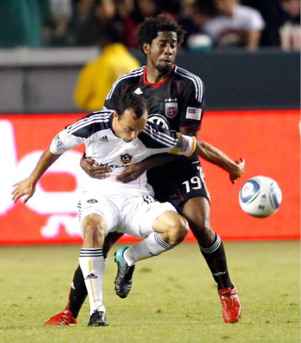 Los Angeles Galaxy's Landon Donovan, left, is held by  D.C. United's Clyde Simms (19) in the second half of an MLS soccer game in Carson, Calif., Saturday, Sept. 18, 2010. The Galaxy won 2-1.  (AP Photo/Lori Shepler)