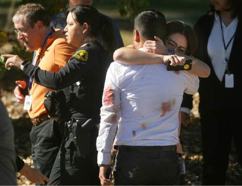 FILE - In this Dec. 2, 2015, file photo, a couple embrace following a shooting that killed multiple people at a social services facility in San Bernardino, Calif. Mass shootings weighed heavily on the minds of Americans in 2015, according to a poll conducted by the Associated Press and the Times Square Alliance. (David Bauman/The Press-Enterprise via AP, File)  MAGS OUT; MANDATORY CREDIT; LOS ANGELES TIMES OUT