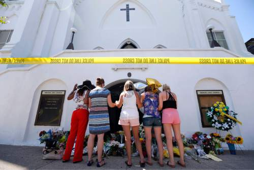 FILE- In this June 18, 2015, file photo, a group of women pray together at a makeshift memorial on the sidewalk in front of the Emanuel AME Church in Charleston, S.C. A single gunman shot and killed several people, including the pastor, at a prayer meeting inside the historic black church. In a poll conducted by the Associated Press and the Times Square Alliance found the most important news events to Americans in the past year were the shootings in Charleston, San Bernardino, Calif., Oregon and Tennessee. (AP Photo/Stephen B. Morton, File)