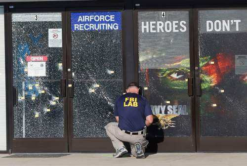 FILE - In this July 17, 2015, file photo, an FBI investigator investigates the scene of a shooting outside a Chattanooga, Tenn., military recruiting center that killed several military personnel. In a poll conducted by the Associated Press and the Times Square Alliance, Americans say the most important events of 2015 were a string of mass shootings, including the attacks in San Bernardino, Chattanooga and Paris. (AP Photo/John Bazemore, File)