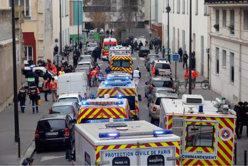 FILE - In this Jan. 7, 2015, file photo, ambulances gather in the street outside the French satirical newspaper Charlie Hebdo's office, in Paris after masked gunmen stormed the offices of the newspaper, killing multiple people. Citing mass shootings like the Charlie Hebdo attack, Americans responding to a poll by the Associated Press and Times Square Alliance said that they felt that 2015 was worse for the world than 2014. (AP Photo/Francois Mori, File)