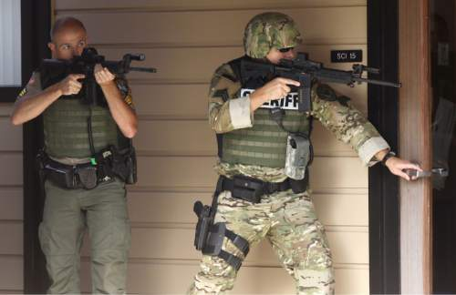 FILE - In this Oct. 1, 2015, file photo, officers in tactical gear respond to a report of a shooting at Umpqua Community College in Roseburg, Ore. In a poll conducted by the Associated Press and the Times Square Alliance, mass shooting events like the one at Umpqua Community College, that killed multiple people, weigh heavily on the mind of Americans. That shooting plus shootings in San Bernardino, Calif, South Carolina, Oregon and Tennessee are among the most important events to Americans in the past year according to those responding tot he poll. (Michael Sullivan /The News-Review via AP, File) MANDATORY CREDIT