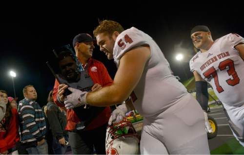 Leah Hogsten     The Salt Lake Tribune Southern Utah Thunderbirds defensive lineman Keyan Norman (54) hands over the rivalry trophy between the two teams in celebration of their win to Southern Utah Thunderbirds head coach Ed Lamb.  Southern Utah University defeated Weber State University 44-0, October 2, 2015 at Stewart Stadium in Ogden.
