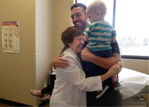 Scott Sommerdorf   |  The Salt Lake Tribune Dr. Vicki L. Macy, MD, OBGYN, hugs Sarah Wangsgard's husband David, after their last pregnancy check-in with her at Salt Lake Regional Medical Center, Wednesday, September 30, 2015. Dr. Macy delivered the Wangsgard's son, Ryan who is being held by David.