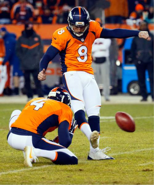 Denver Broncos kicker Brandon McManus (8) unsuccessfully attempts a game-winning field goal as punter Britton Colquitt (4) holds during the second half of an NFL football game against the Cincinnati Bengals, Monday, Dec. 28, 2015, in Denver. (AP Photo/Jack Dempsey)