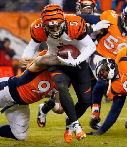 Cincinnati Bengals quarterback AJ McCarron (5) is tackled by Denver Broncos defensive end Derek Wolfe (95) during the second half of an NFL football game, Monday, Dec. 28, 2015, in Denver. (AP Photo/Jack Dempsey)