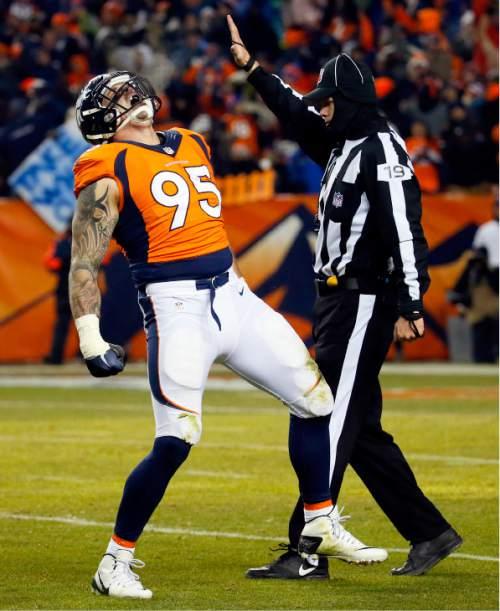 Denver Broncos defensive end Derek Wolfe (95) celebrates his tackle on Cincinnati Bengals quarterback AJ McCarron during the second half of an NFL football game, Monday, Dec. 28, 2015, in Denver. (AP Photo/Jack Dempsey)
