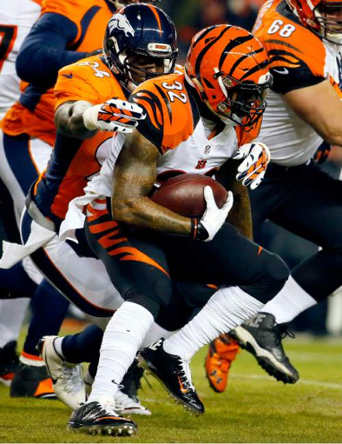 Cincinnati Bengals running back Jeremy Hill (32) is tackled by Denver Broncos outside linebacker DeMarcus Ware (94) during the first half of an NFL football game, Monday, Dec. 28, 2015, in Denver. (AP Photo/Jack Dempsey)