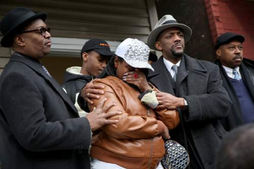 LaTarsha Jones, center, the daughter of Bettie Jones, is comforted by family and friends during a press conference on Sunday, Dec. 27, 2015, in front of the house where Bettie Jones was killed Saturday in the West Garfield Park neighborhood of Chicago. Grieving relatives and friends of two people shot and killed by Chicago police said Sunday that the city's law enforcement officers had failed its residents. (Nancy Stone/Chicago Tribune via AP) MANDATORY CREDIT