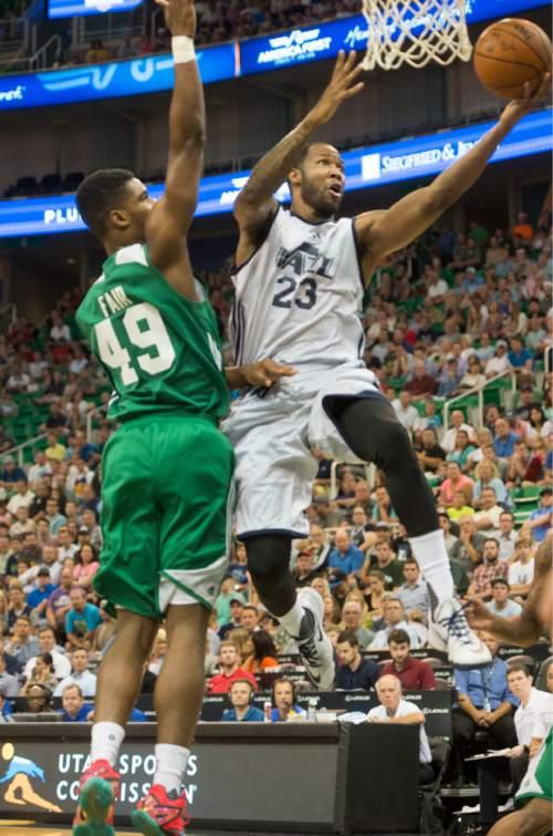 Rick Egan  |  The Salt Lake Tribune  Utah Jazz forward Chris Johnson (23) takes the ball to the hoop, as  Boston forward C.J. Fair (49) defends, in Summer League action, Utah Jazz vs. The Boston Celtics, at EnergySolutions Arena, Monday, July 6, 2015.