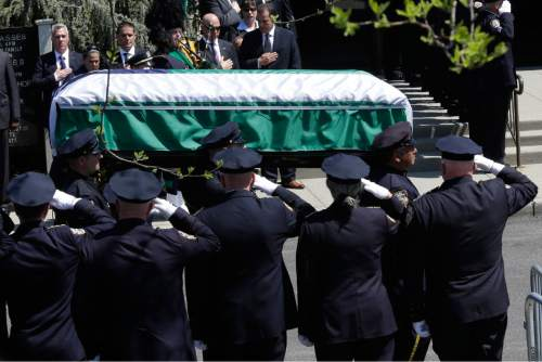 Police officers salute as the casket carrying the remains of New York Police Department Officer Brian Moore arrives for his funeral Mass, Friday, May 8, 2015, at the St. James Roman Catholic Church in Seaford, N.Y. The 25-year-old died Monday, two days after he was shot in Queens, while on patrol. (AP Photo/Mary Altaffer)