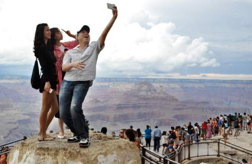FILE - In this Aug. 2, 2015, file photo, tourists Joseph Lin, Ning Chao, center, and Linda Wang, left, pose for a selfie along the south rim at Grand Canyon National Park, Ariz. The throngs of tourists have been showing up in big numbers at other national parks, including Yellowstone in Wyoming, Yosemite in California and Zion in Utah, driven by good weather, cheap gas and marketing campaigns ahead of next year's National Park Service centennial. (Emery Cowan/Arizona Daily Sun via AP) MANDATORY CREDIT