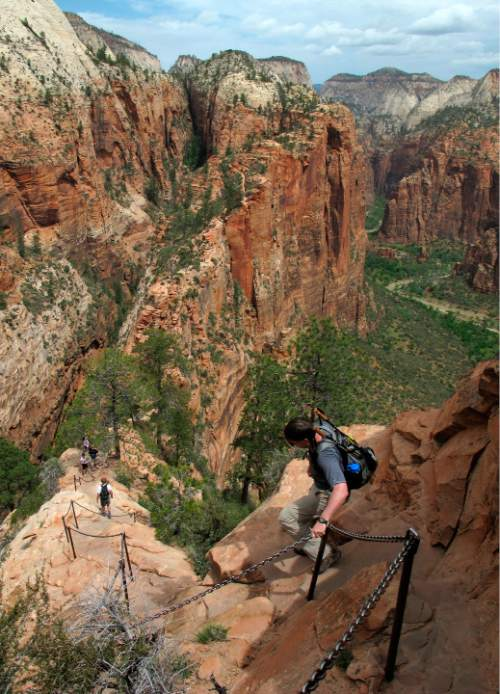 FILE - In this May 8, 2011, file photo, hikers climb down the Angels Landing trail in Zion National Park, in Utah. Crowds are flocking in record numbers to Zion National Park this year, with visitation up 28 percent in the first quarter of 2015. The National Park Service celebrates its 100th birthday in 2016 and has been urging Americans to rediscover the country's scenic wonders or find new parks to visit through marketing campaigns that include giving free passes to every fourth-grader and their families. (Jud Burkett /The Spectrum & Daily News via AP, File)