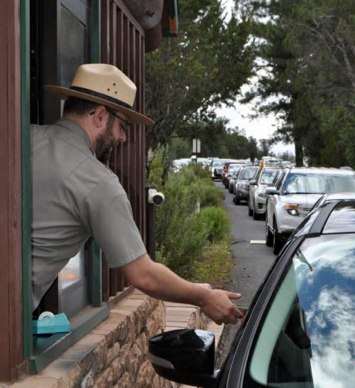 FILE - In this Aug. 2, 2015, file photo, Nate Powell, an employee with Grand Canyon National Park, collects an entrance fee as traffic is backed up as vehicles arrive at an entrance gate at Grand Canyon National Park, Ariz. Many of the country's most prominent national parks, including Grand Canyon, Yellowstone and Zion, set new visitation records in 2015. (Emery Cowan/Arizona Daily Sun via AP, File) MANDATORY CREDIT