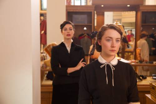 """Eilis (Saoirse Ronan, right) is an Irish immigrant who gets a job in a New York department store, under the watchful eye of Miss Fontini (Jessica Paré), in the drama """"Brooklyn."""" Courtesy Fox Searchlight Pictures"""