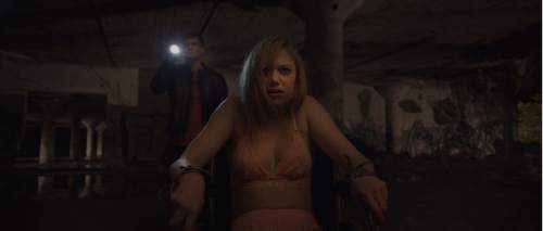 """Jay (Maika Monroe, foreground) is tied up by Hugh (Jake Weary), about to face a supernatural enemy in the horror thriller ìIt Follows."""" Radius/TWC"""
