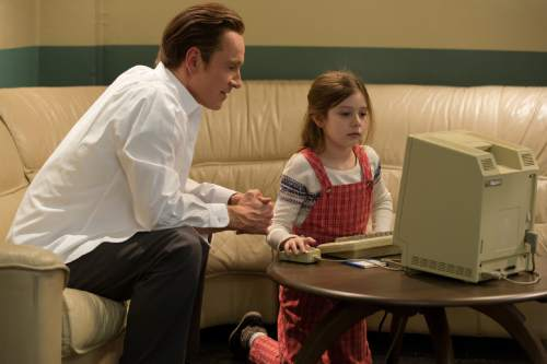 """In this image released by Universal Pictures, Michael Fassbender, left, as Steve Jobs and Makenzie Moss as a young Lisa Jobs, appear in a scene from the film, """"Steve Jobs.""""  (Francois Duhamel/Universal Pictures via AP)"""