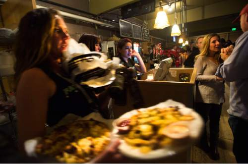 Steve Griffin  |  The Salt Lake Tribune  Fats Grill owner Mishelle Caligiuri, right,  talks with guest as the bar staff serves up food and drink during the bar's last night of business in Salt Lake City, Wednesday, December 30, 2015. The long time bar and grill will be torn down and be replaced by a office tower.