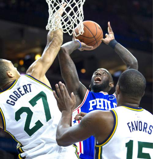 Philadelphia 76ers' JaKarr Sampson takes a shot past Utah Jazz's Rudy Gobert (27) and Derrick Favors (15) in the first half of an NBA basketball game, Friday, Oct. 30, 2015, in Philadelphia. (AP Photo/Laurence Kesterson)
