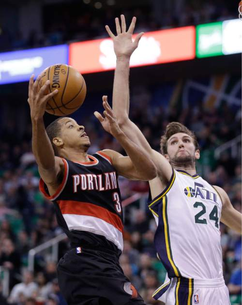 Portland Trail Blazers guard C.J. McCollum (3) goes to the basket as Utah Jazz center Jeff Withey (24) defends during the second quarter of an NBA basketball game Thursday, Dec. 31, 2015, in Salt Lake City. (AP Photo/Rick Bowmer)