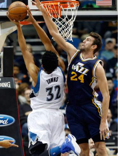 Utah Jazz's Jeff Withey, right, attempts to block a shot by Minnesota Timberwolves' Karl-Anthony Towns in the first quarter of an NBA basketball game Wednesday, Dec. 30, 2015, in Minneapolis. (AP Photo/Jim Mone)
