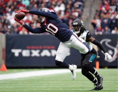 Houston Texans wide receiver DeAndre Hopkins (10) makes a catch in front of Jacksonville Jaguars strong safety Johnathan Cyprien (37) during the first half of an NFL football game Sunday, Jan. 3, 2016, in Houston. (AP Photo/Eric Christian Smith)
