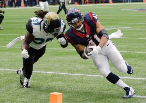 Houston Texans running back Jonathan Grimes (41) scores on a 12-yard as Jacksonville Jaguars strong safety Johnathan Cyprien (37) tires to make a stop during the first half an NFL football game Sunday, Jan. 3, 2016, in Houston. (AP Photo/David J. Phillip)