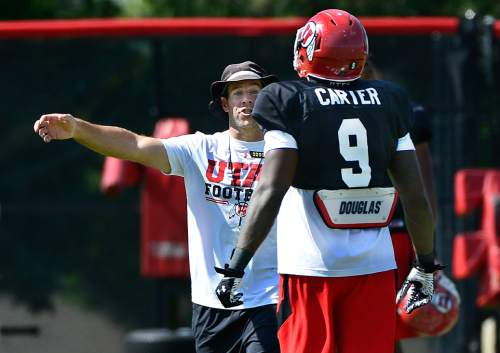 Scott Sommerdorf   |  The Salt Lake Tribune Utah safties coach Morgan Scalley talks with S Tevin Carter after a play at Utah football practice with pads on the baseball field, Thursday, August 7, 2014.