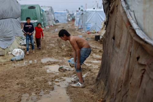 In this picture taken Monday, Jan. 4, 2016, a Syrian refugee boy lifts up his jeans to walks through mud from the heavy rain, at a refugee camp at a refugee camp in the town of Hosh Hareem, in the Bekaa valley, east Lebanon. A snowstorm engulfed Lebanon on the first day of the new year, cutting off mountain roads, isolating villages and worsening living conditions for tens of thousands of Syrian refugees. (AP Photo/Hassan Ammar)
