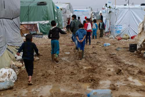 In this picture taken Monday, Jan. 4, 2016, Syrian refugee children walk in mud from the heavy rain at a refugee camp in the town of Hosh Hareem, in the Bekaa valley, east Lebanon. A snowstorm engulfed Lebanon on the first day of the new year, cutting off mountain roads, isolating villages and worsening living conditions for tens of thousands of Syrian refugees. (AP Photo/Hassan Ammar)
