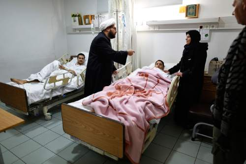 In this picture taken Wednesday, Dec. 30, 2015, Muslim Shiite clerics visit pro-government Syrian fighters who were evacuated from the villages of Foua and Kfarya, as they lay in beds in a hospital south of Beirut run by the militant Hezbollah group. Pro-government Syrian fighters who were recently evacuated from two besieged Shiite villages in northern Syria say residents there live under harsh human conditions where people can hardly find medicine or even food to eat making some rely on grass in order to survive.  (AP Photo/Hassan Ammar)