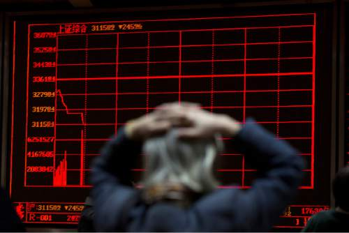 A woman reacts near a display board showing the plunge in the Shanghai Composite Index at a brokerage in Beijing, China, Thursday, Jan. 7, 2016. Chinese stocks nosedived on Thursday, triggering the second daylong trading halt of the week and sending other Asian markets sharply lower as investor jitters rippled across the region. (AP Photo/Ng Han Guan)