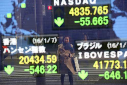 A woman is reflected on an electronic stock board of a securities firm in Tokyo, Thursday, Jan. 7, 2016. Chinese stocks nose dived on Thursday, triggering the second daylong trading halt of the week and sending share markets, currencies and oil prices lower as investor jitters rippled across Asia.(AP Photo/Eugene Hoshiko)