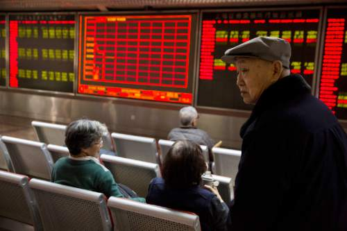 Investors gather near a display board showing the plunge in the Shanghai Composite Index at a brokerage in Beijing, China, Thursday, Jan. 7, 2016. Chinese stocks nosedived on Thursday, triggering the second daylong trading halt of the week and sending other Asian markets sharply lower as investor jitters rippled across the region. (AP Photo/Ng Han Guan)
