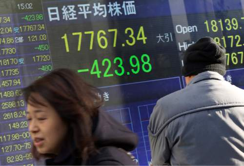 A man, right, looks at an electronic stock board of a securities firm in Tokyo, Thursday, Jan. 7, 2016. Chinese stocks nose dived on Thursday, triggering the second daylong trading halt of the week and sending share markets, currencies and oil prices lower as investor jitters rippled across Asia.(AP Photo/Eugene Hoshiko)