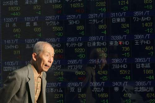 A man walks past an electronic stock board of a securities firm in Tokyo, Thursday, Jan. 7, 2016. Chinese stocks nose dived on Thursday, triggering the second daylong trading halt of the week and sending share markets, currencies and oil prices lower as investor jitters rippled across Asia.(AP Photo/Eugene Hoshiko)