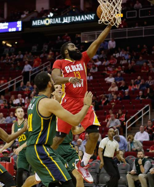 Houston Rockets guard James Harden (13) drives past Utah Jazz forward Trey Lyles (41) for a layup during the first half of an NBA basketball game Thursday, Jan. 7, 2016, in Houston. (AP Photo/Bob Levey)